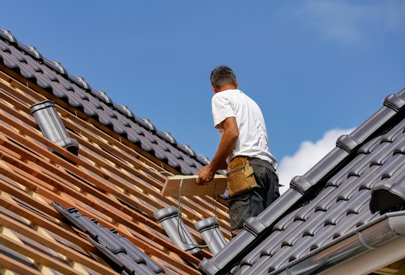 Takläggare står på taket och lägger nytt tak.