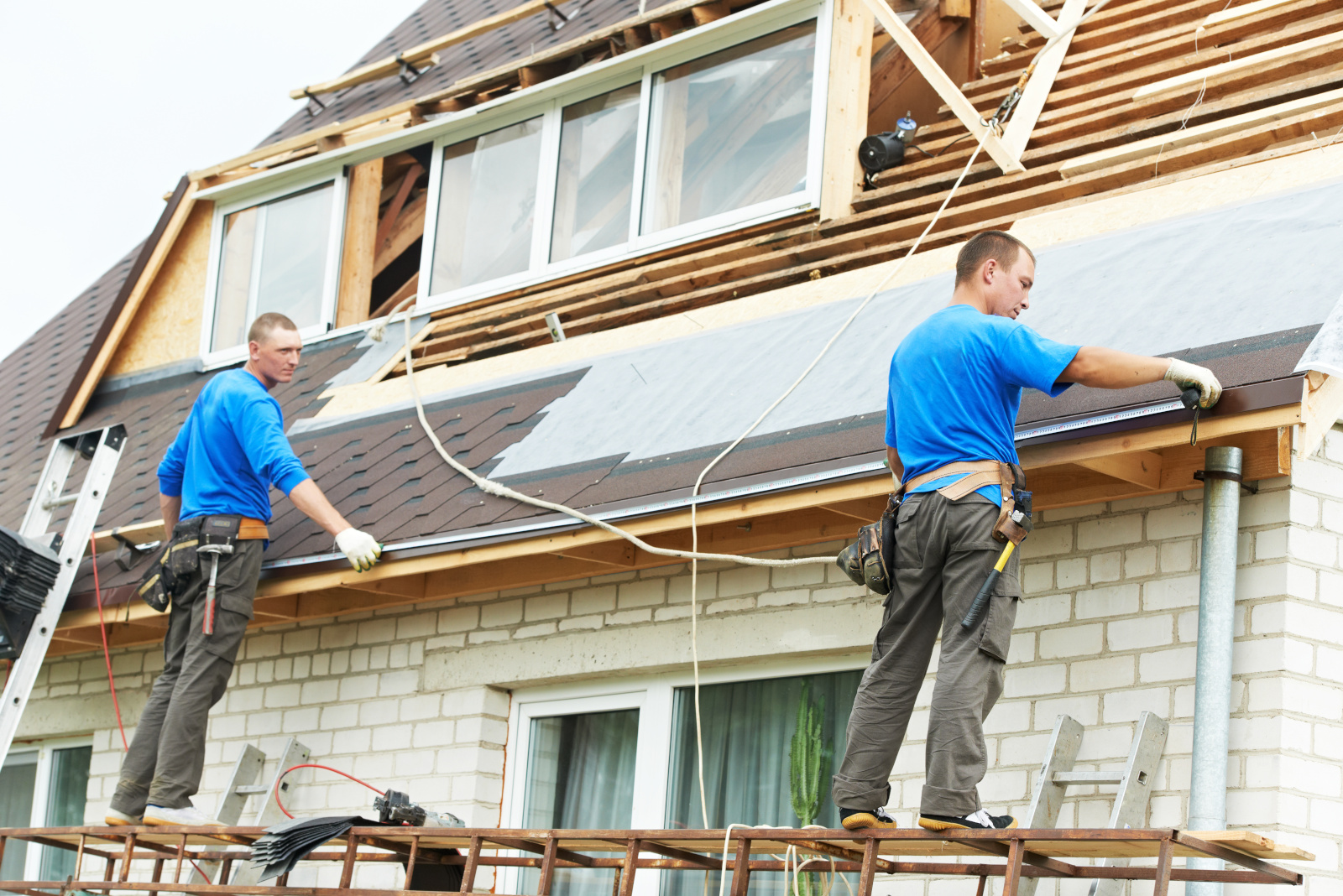 Två takläggare mäter takets bredd utomhus.