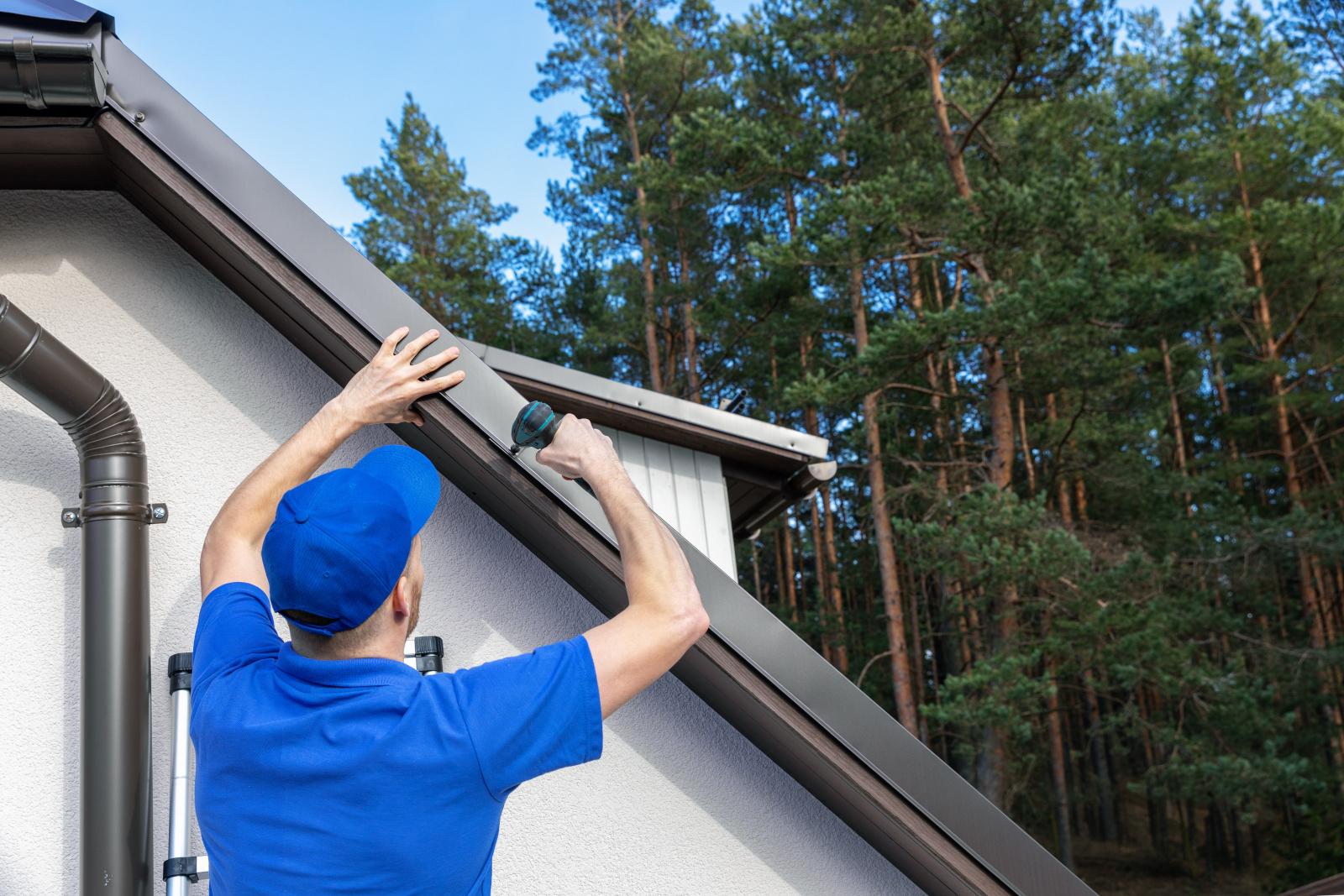 Takläggaren skruvar fast nytt tak på huset.