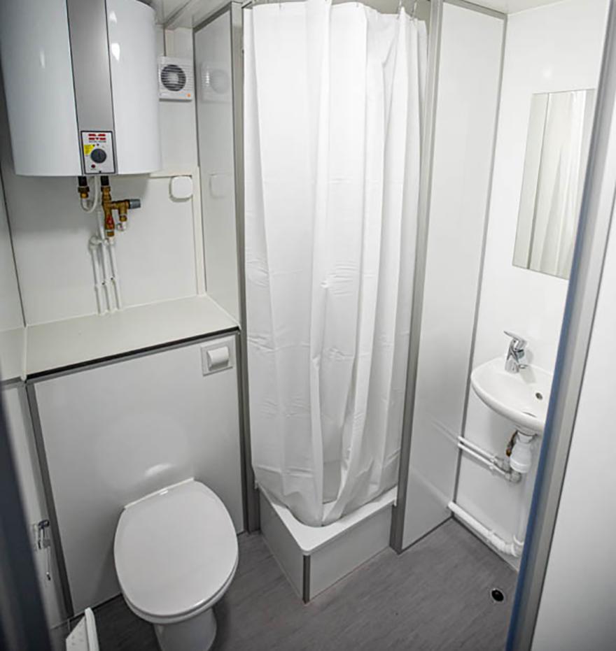 Ett badrum med dusch och toalett i en arbetsvagn.