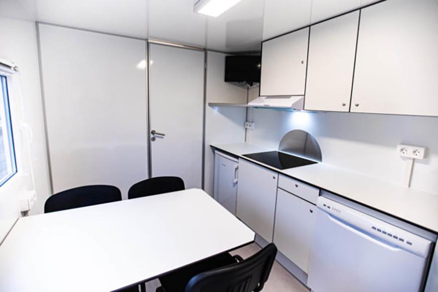 Ett kök inuti en arbetsvagn. Där finns spisplattor, kylskåp, bord med fyra stolar och diskmaskin.
