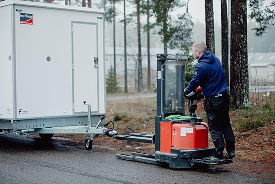 En man flyttar en arbetsvagn.