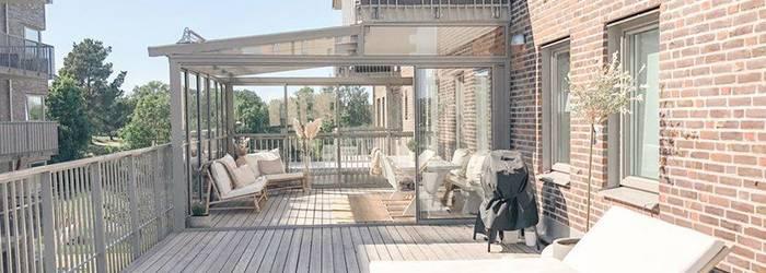 Stor, delvis inglasad balkong, med balkongmöbler.