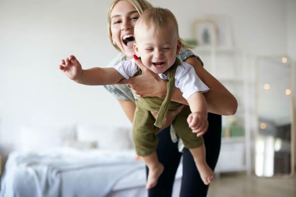 En kvinna som skrattar med ett barn i handen
