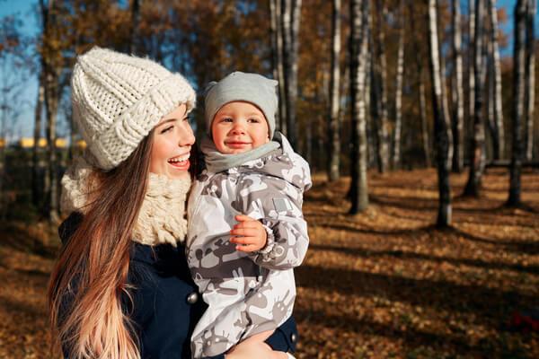 Glad kvinna håller i ett barn