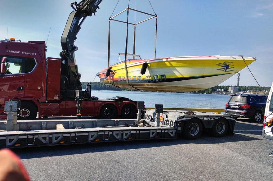 En röd kranbil lyfter en gul båt inför båttransport.