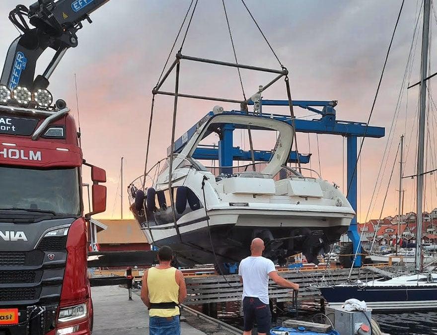 En röd kranbil lyfter en motorbåt inför båttransport.