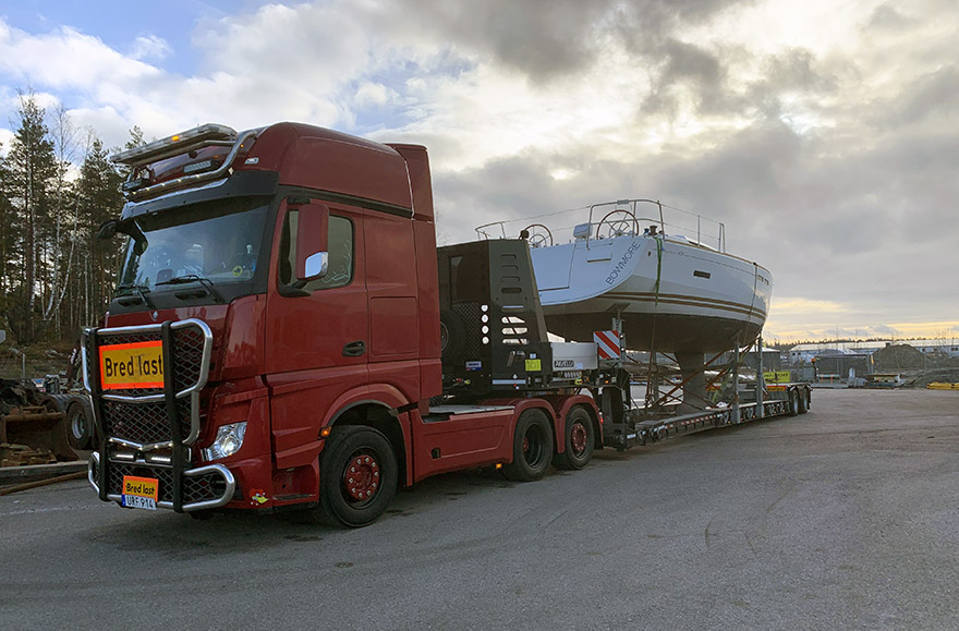 En röd lastbil kör en båttransport.
