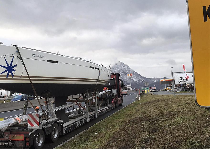 En båttransport på en väg med ett högt berg i bakgrunden.