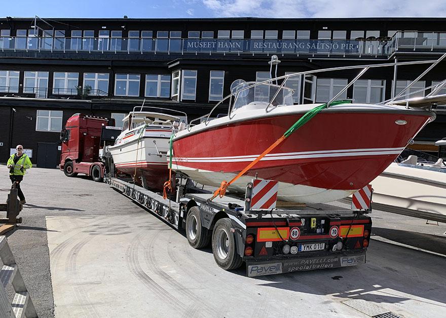 En röd lastbil kör en dubbel båttransport, med två båtar på lasten.