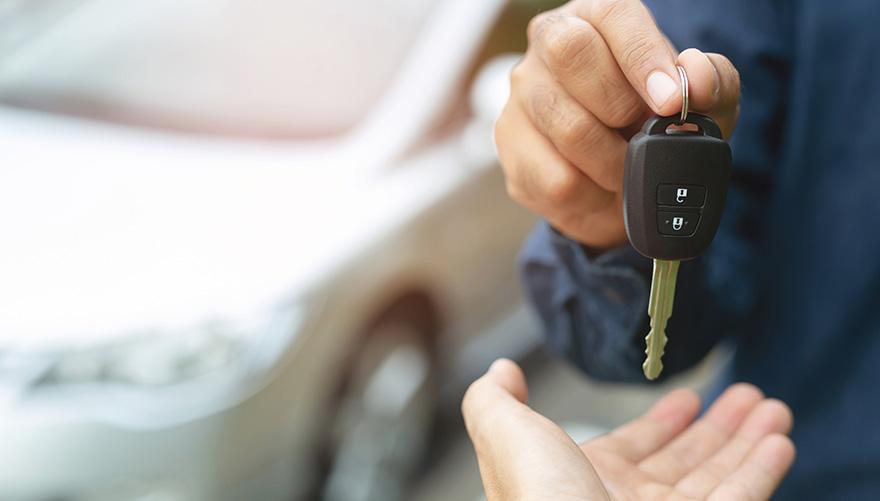 En person som sålt en begagnad bil räcker över nycklarna till den nya ägaren.