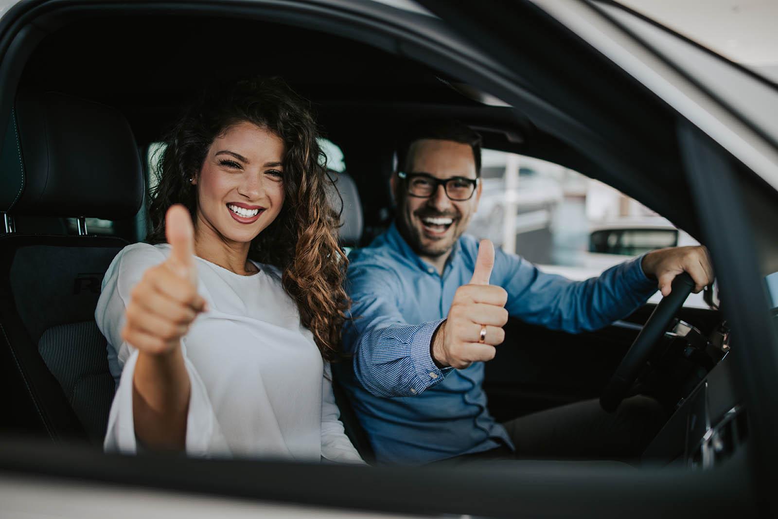 En man och en kvinna i en bil ler och gör tummen upp.