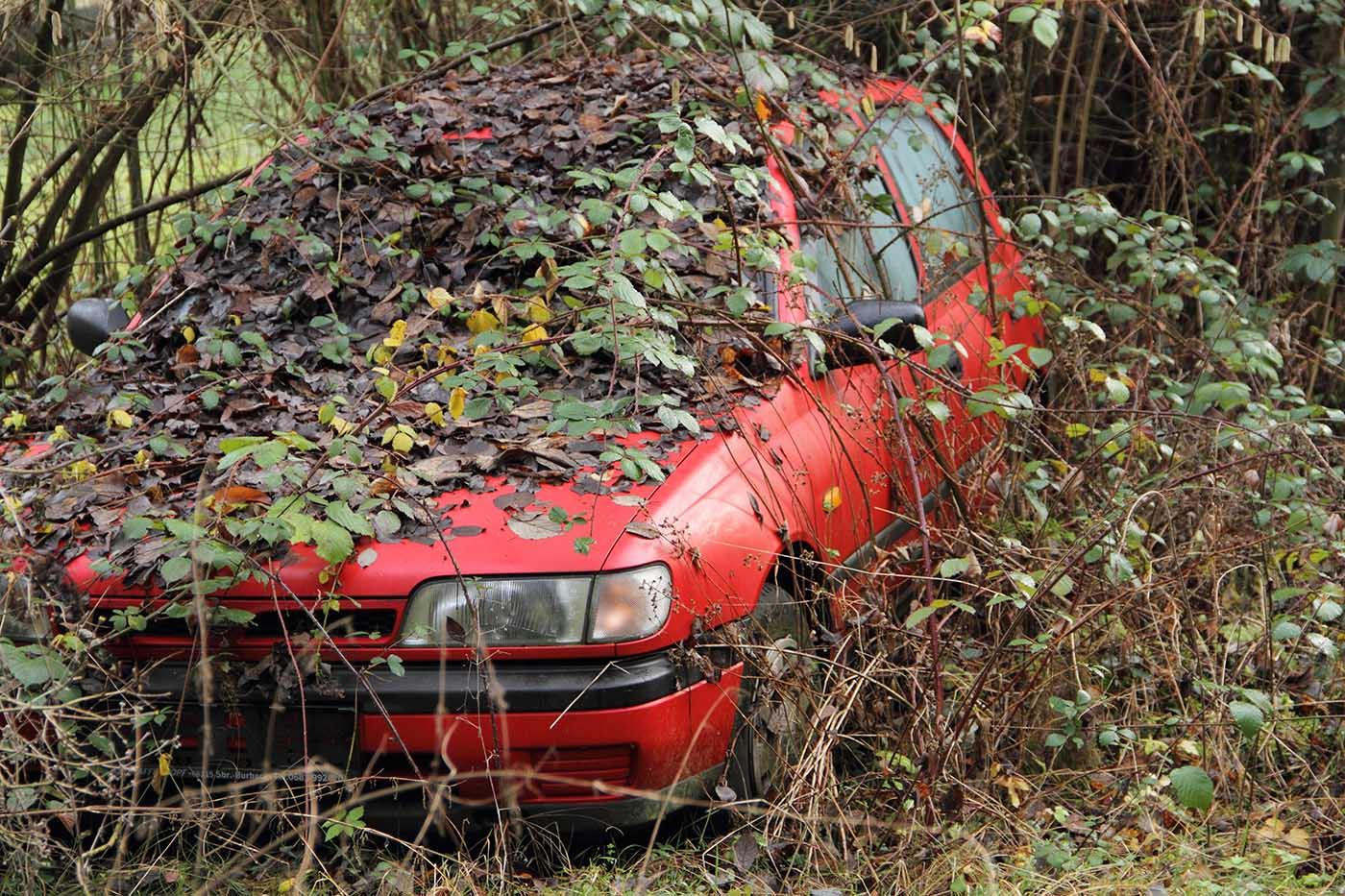 Avställd röd bil för transport till vår bilskrot i Stockholms län.