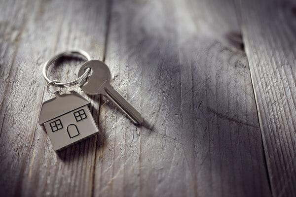 Nycklar med nyckelring ligger på ett träbord