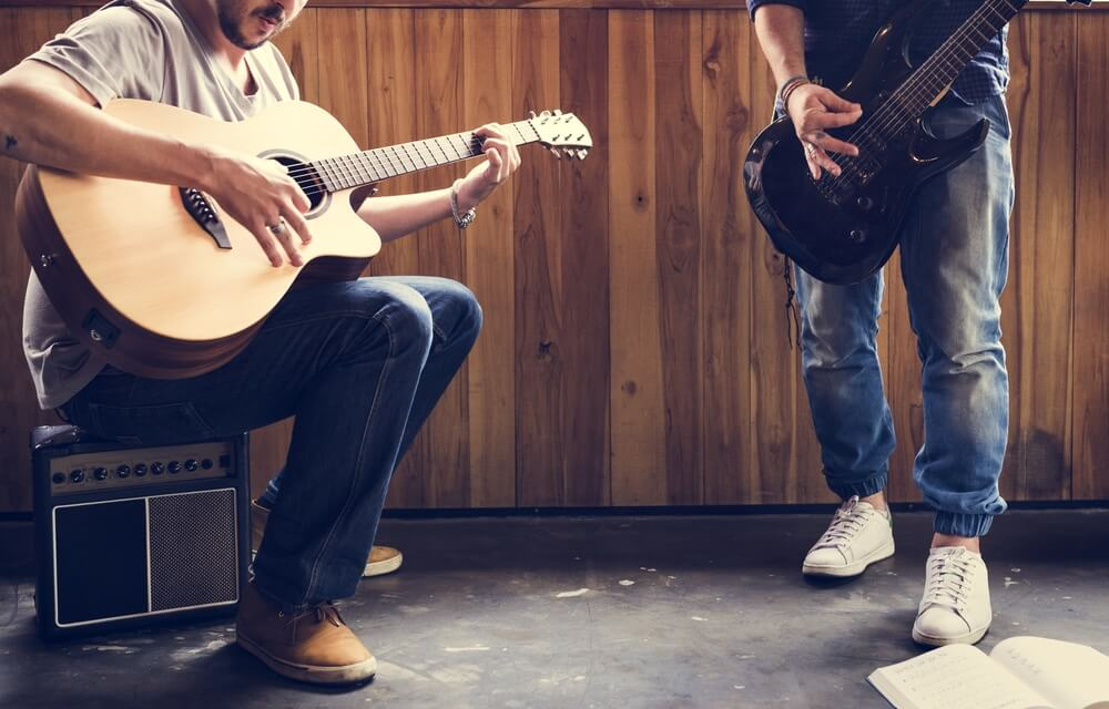 två killar spelar gitarr