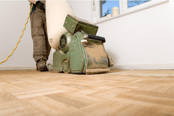 En arbetare slipar golvet