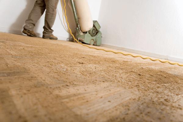 Arbetare slipar golvet med en slipmaskin