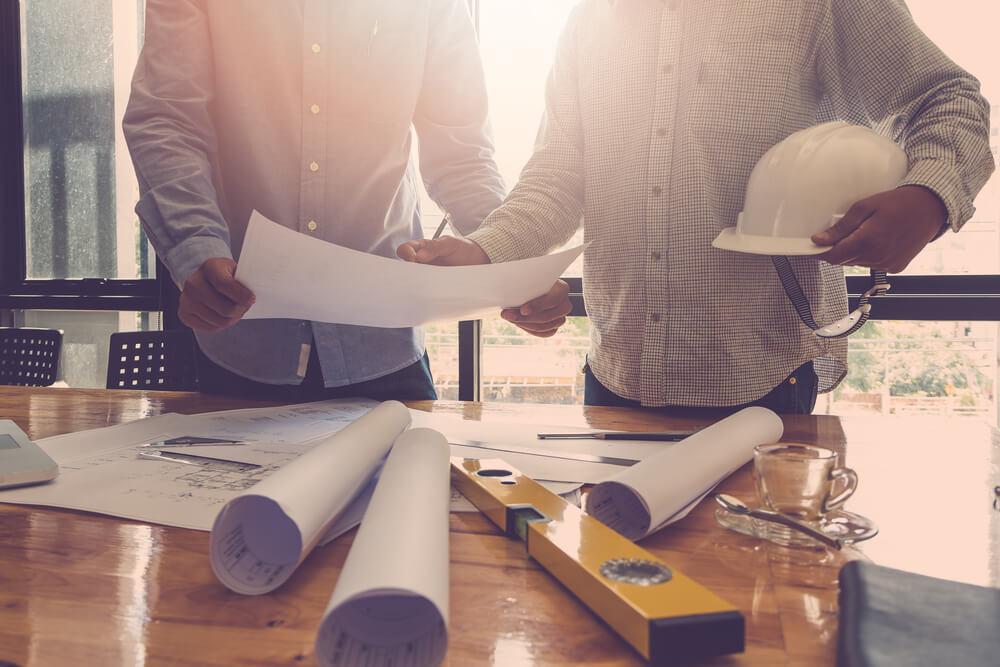 byggarbetare inspekterar ritning
