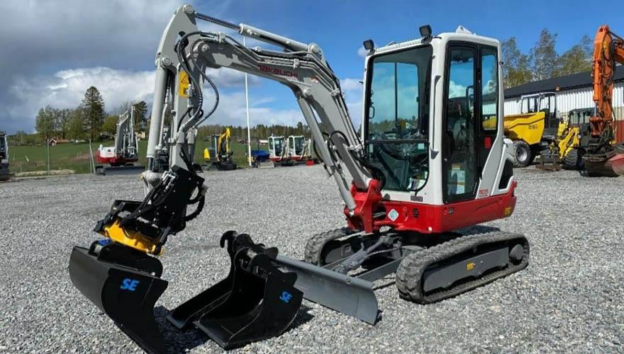 En av våra grävskopor står på en grusplan med ett antal andra maskiner i bakgrunden.