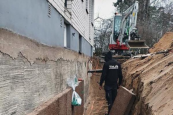 TMJ utför dränering i Karlstad. På bilden syns en anställd stå i ett dike som är grävt intill husväggen. I bakgrunden syns en grävskopa.