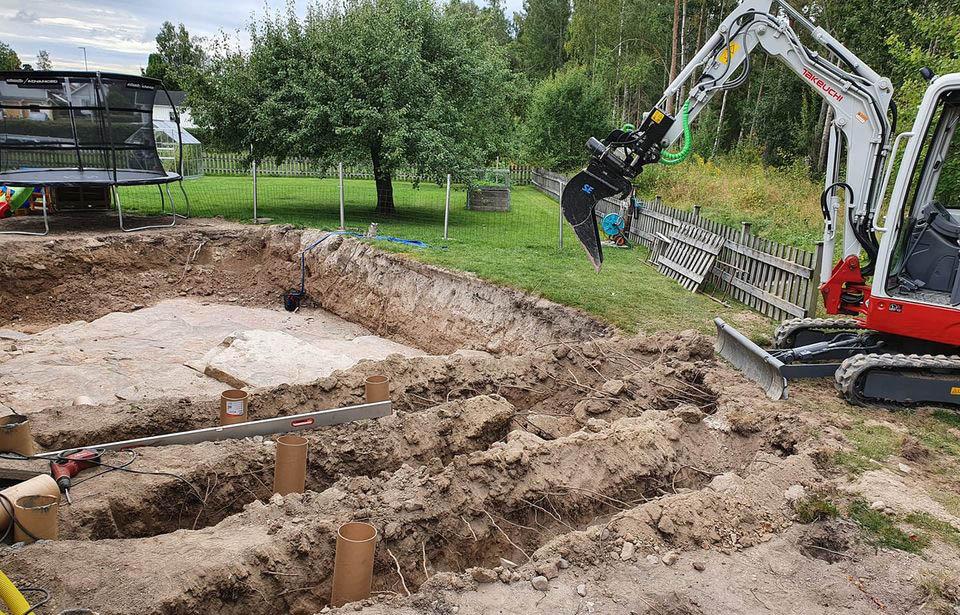 Dränering i Karlstad. En grävskopa står vid en uppgrävd gräsmatta på en villatomt.