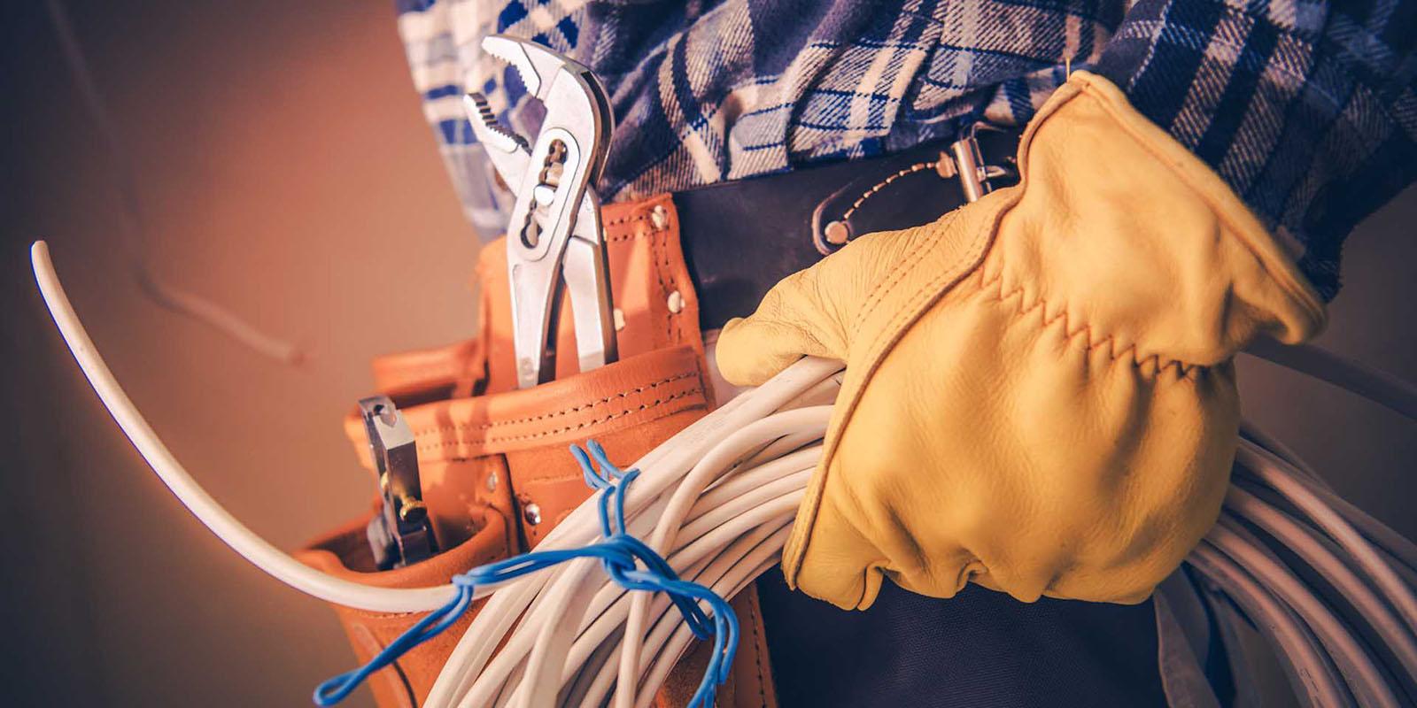 Närbild på elektriker som har på sig ett orange verktygsbälte och håller i en ihoprullad kabel.