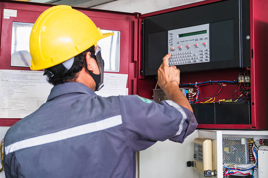En elektriker i gul hjälm undersöker ett larmsystem.