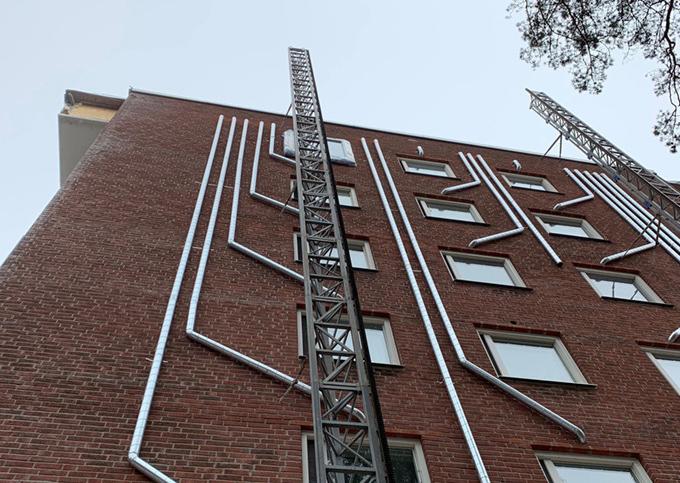 Energieffektivisering på en fastighet i Södertälje. Tilluftskanaler har monterats på utsidan av tegelfasaden.