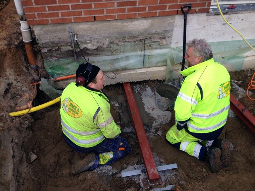 Två män arbetar med att dränera en husgrund.