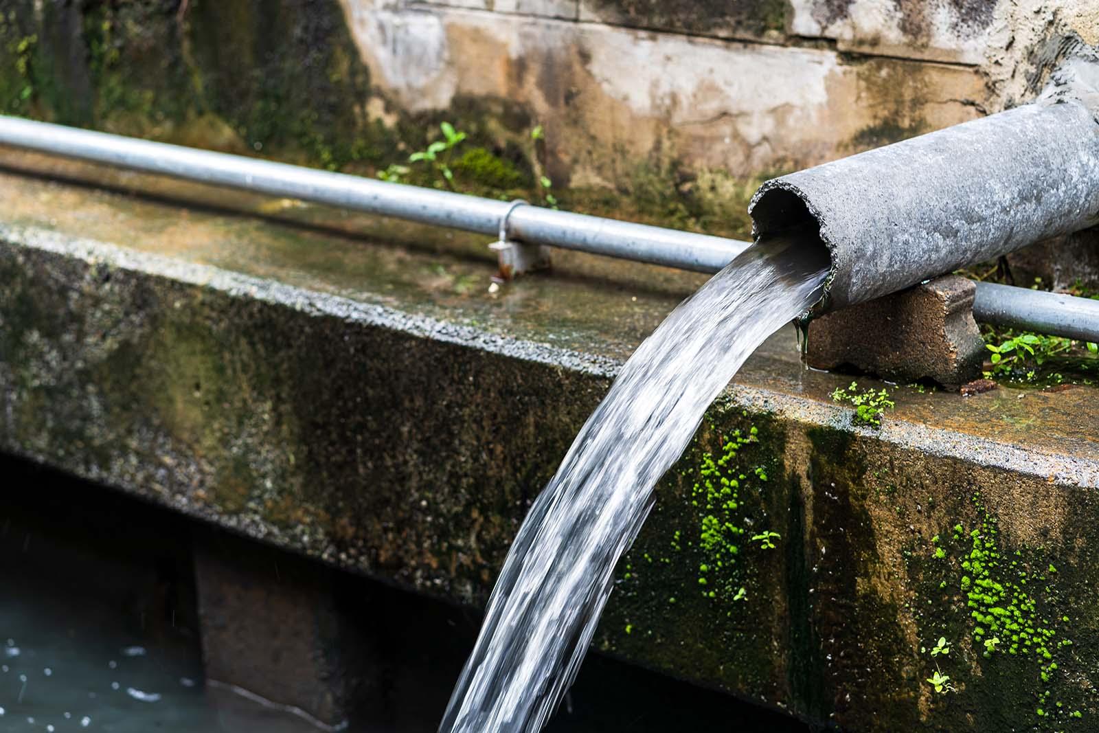 Behöver du hjälp att installera enskilt avlopp i Stockholm? Då är du i trygga händer! På bilden ett rör med vatten som forsar ut och leds vidare.