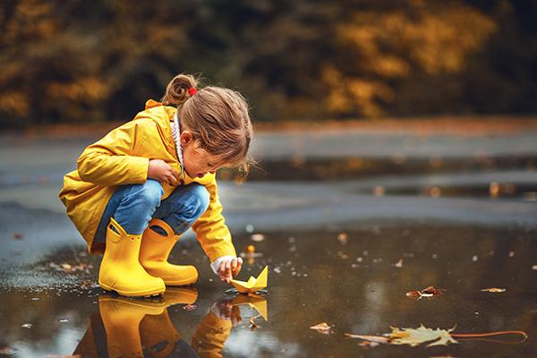 flicka med pappersbåt vid pöl på hösten