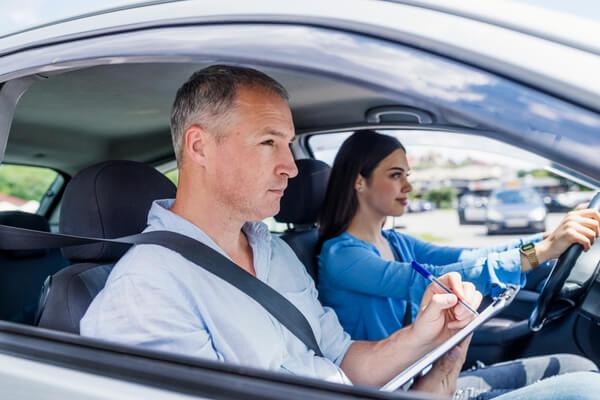 En kvinna sitter med en trafiklärare i bilen.
