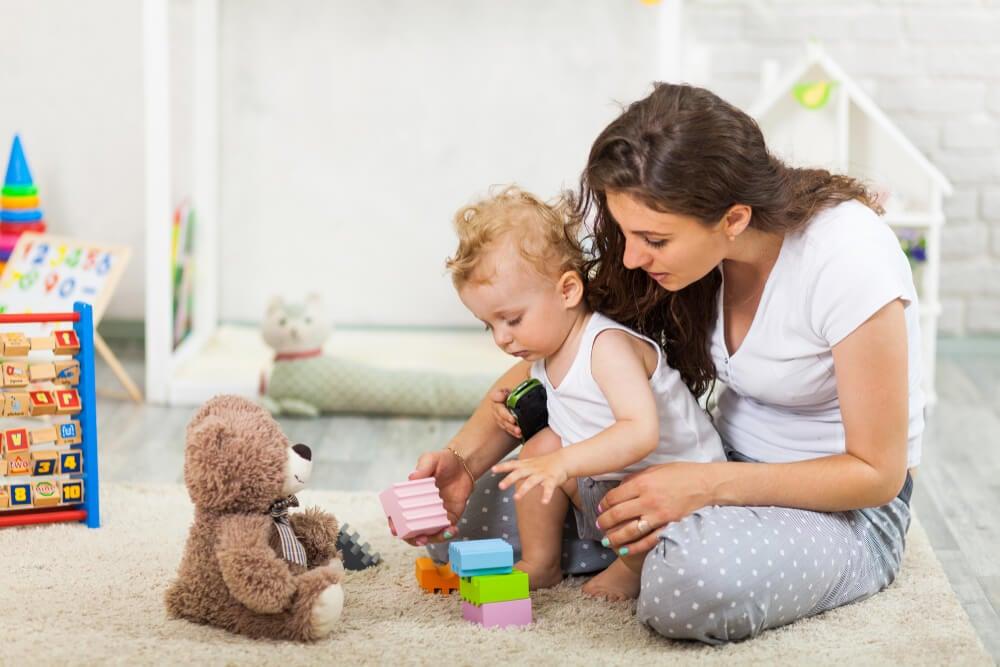barn och mamma leker med klossar