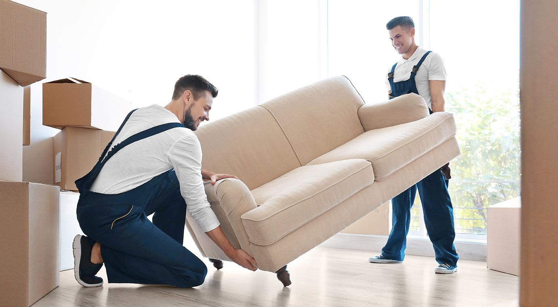 Två flyttgubbar flyttar en soffa.