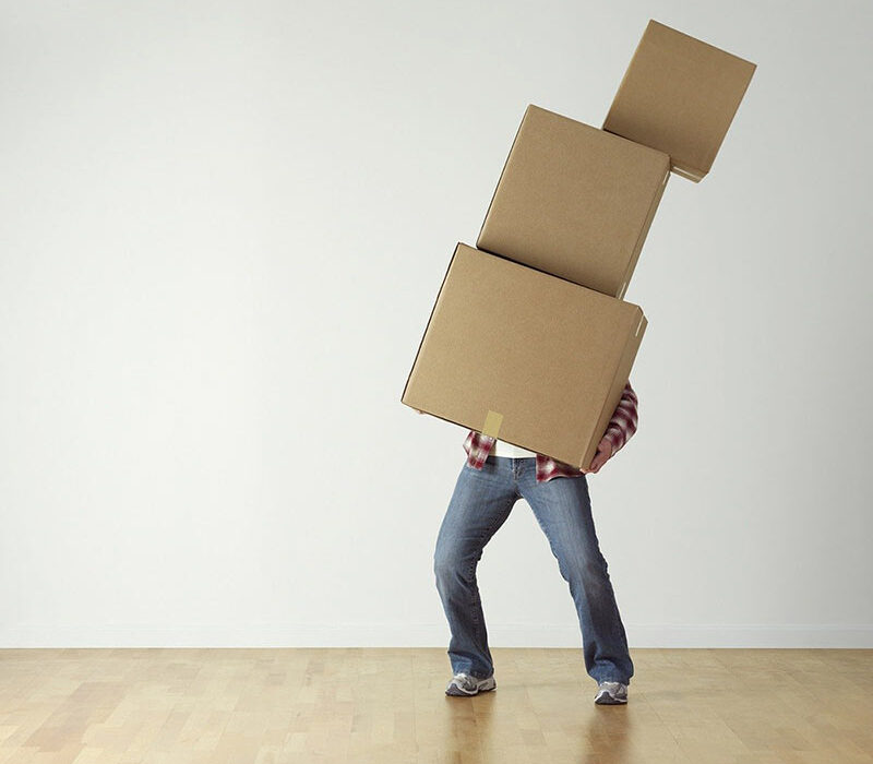 En person balanserar ett torn med flyttkartonger i famnen.