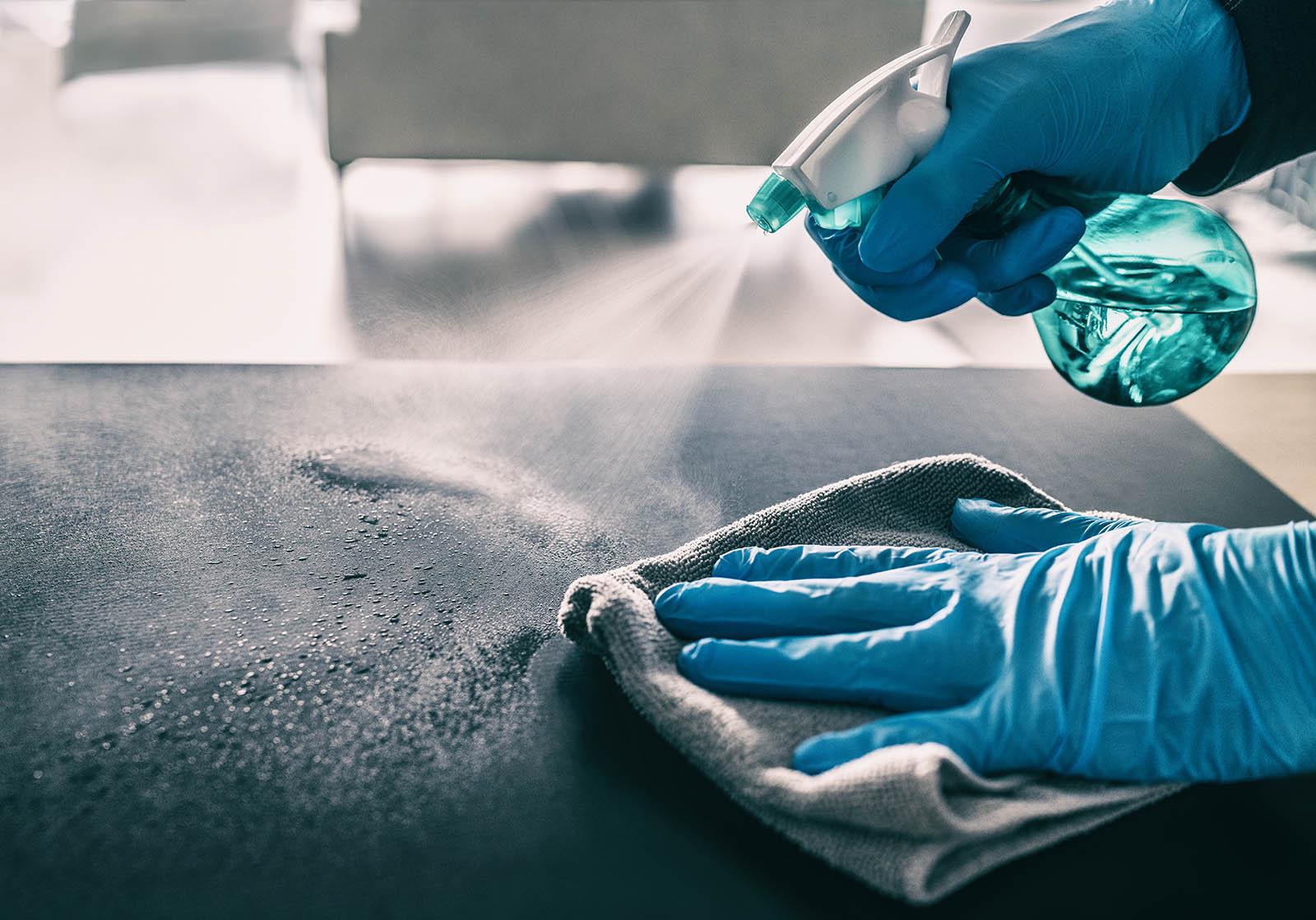 En person med plasthandskar sprejar rengöringsspray och torkar av en yta.