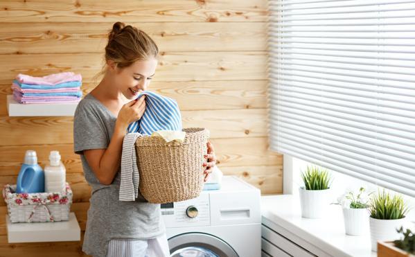 Kvinna med ren tvätt från tvättmaskin