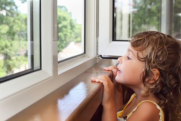 flicka ser ut genom nya fönster
