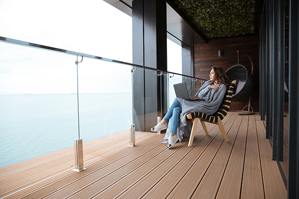 kvinna sitter på balkong med glasräcke