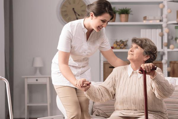 Äldre kvinna får hjälp med att ställa sig upp