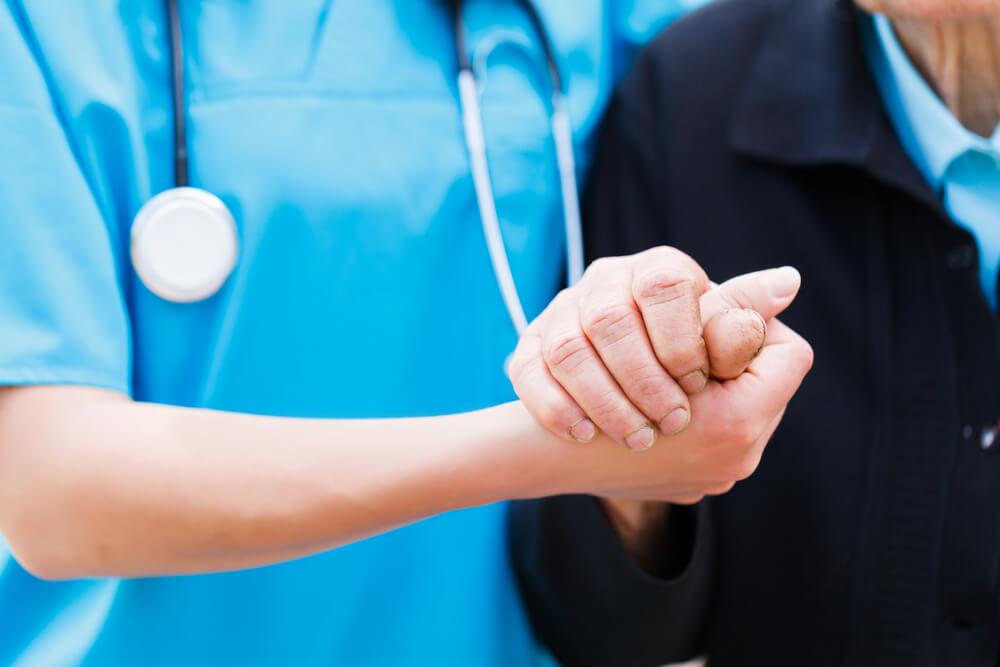 sjuksköterska håller hand med äldre person