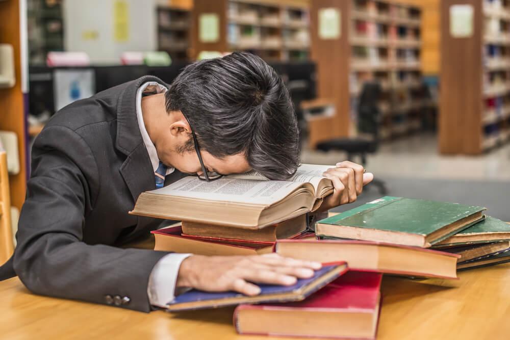 juriststudent ligger äver böcker