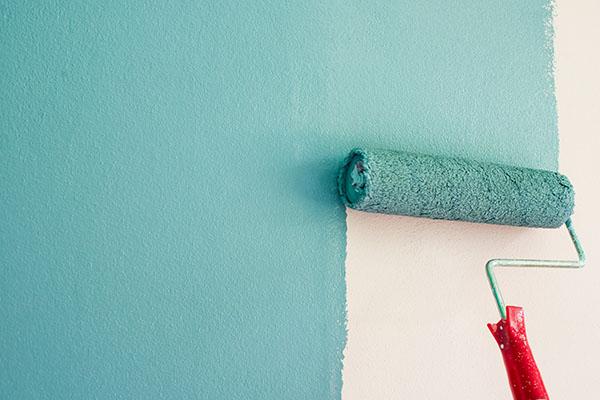 roller med blågrön nyans målar i lägenhet på Lidingö