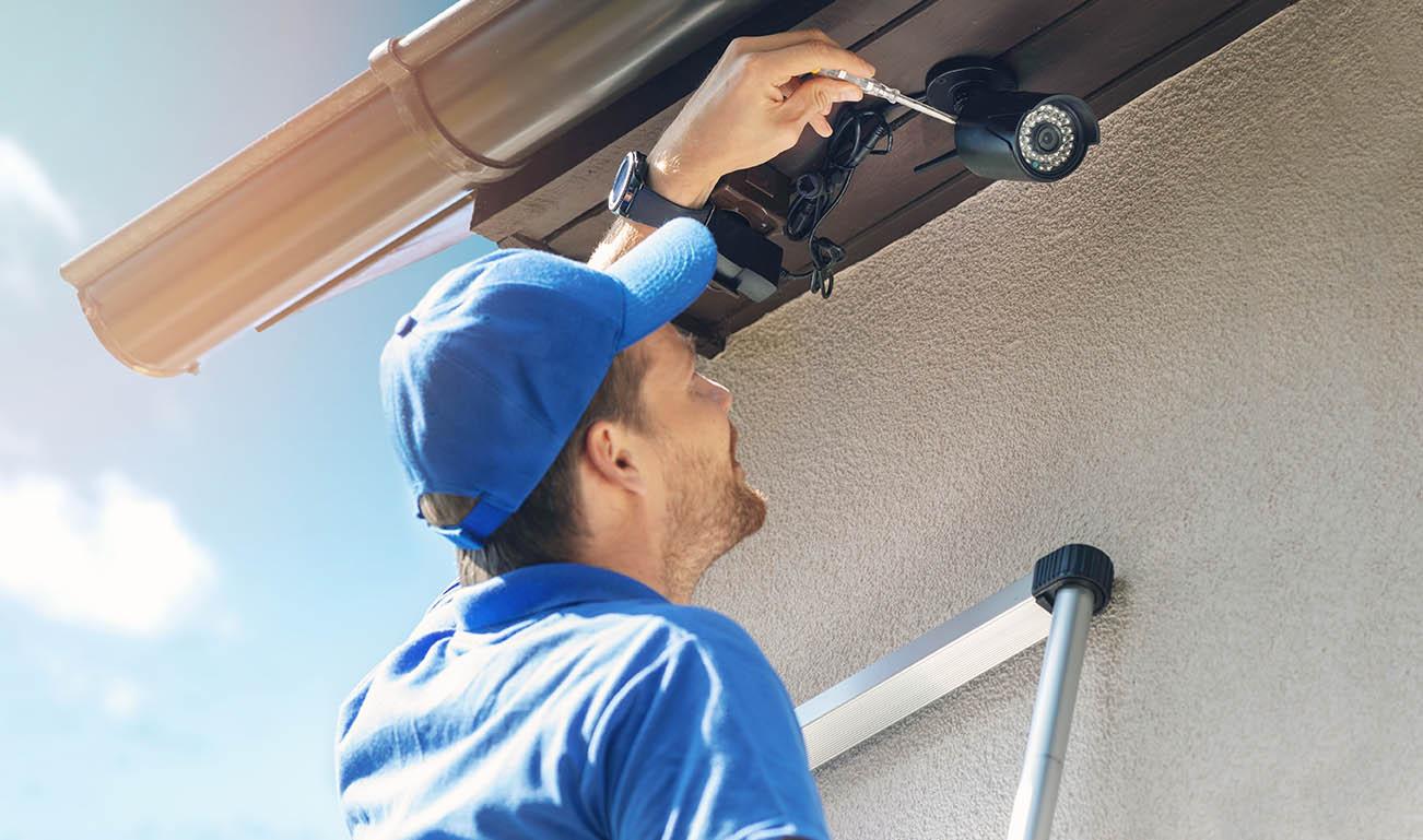 En man i blå arbetskläder och keps skruvar upp kameraövervakning på ett hus.