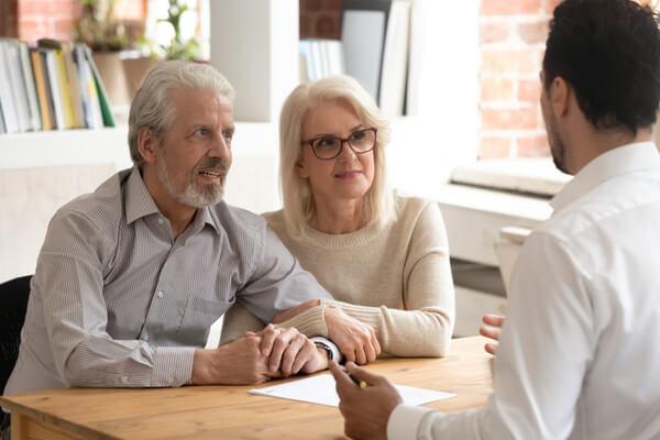 Glada äldre par sitter vid bordet och pratar med en man