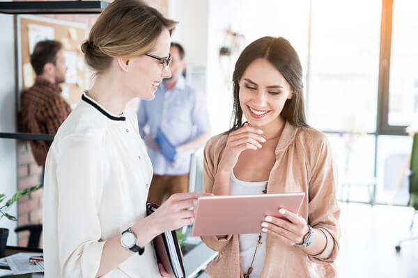 två kvinnor kollar på iPaden