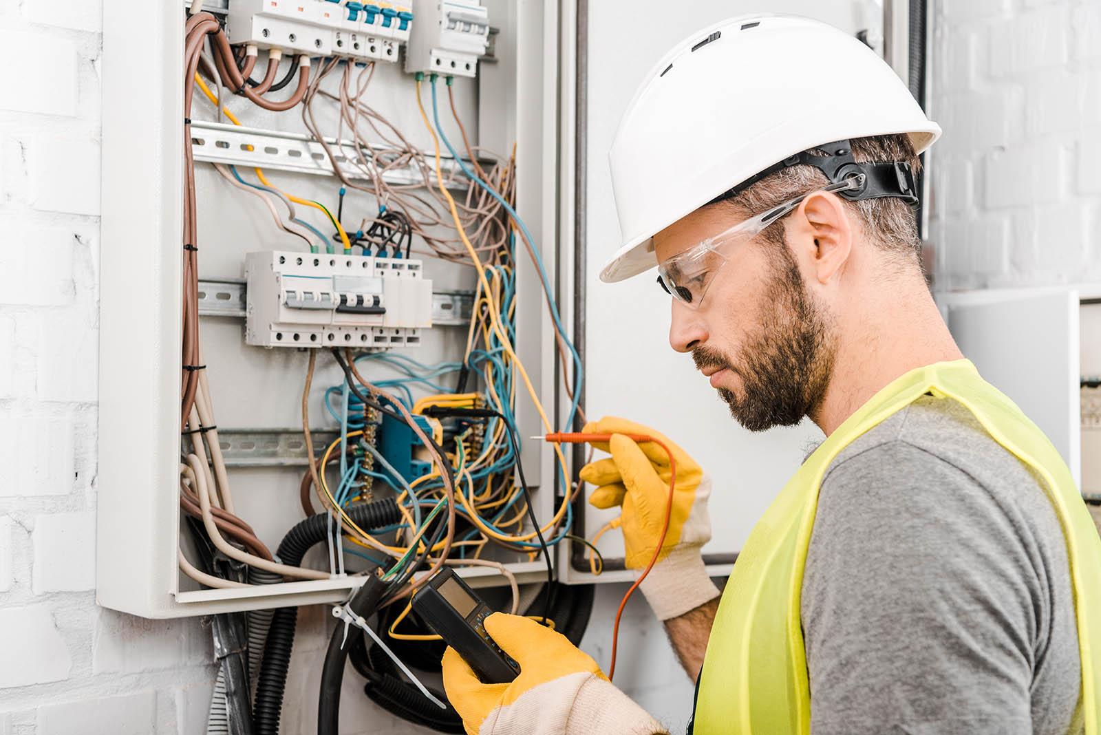 En elektriker i vit hjälm jobbar vid ett elskåp.