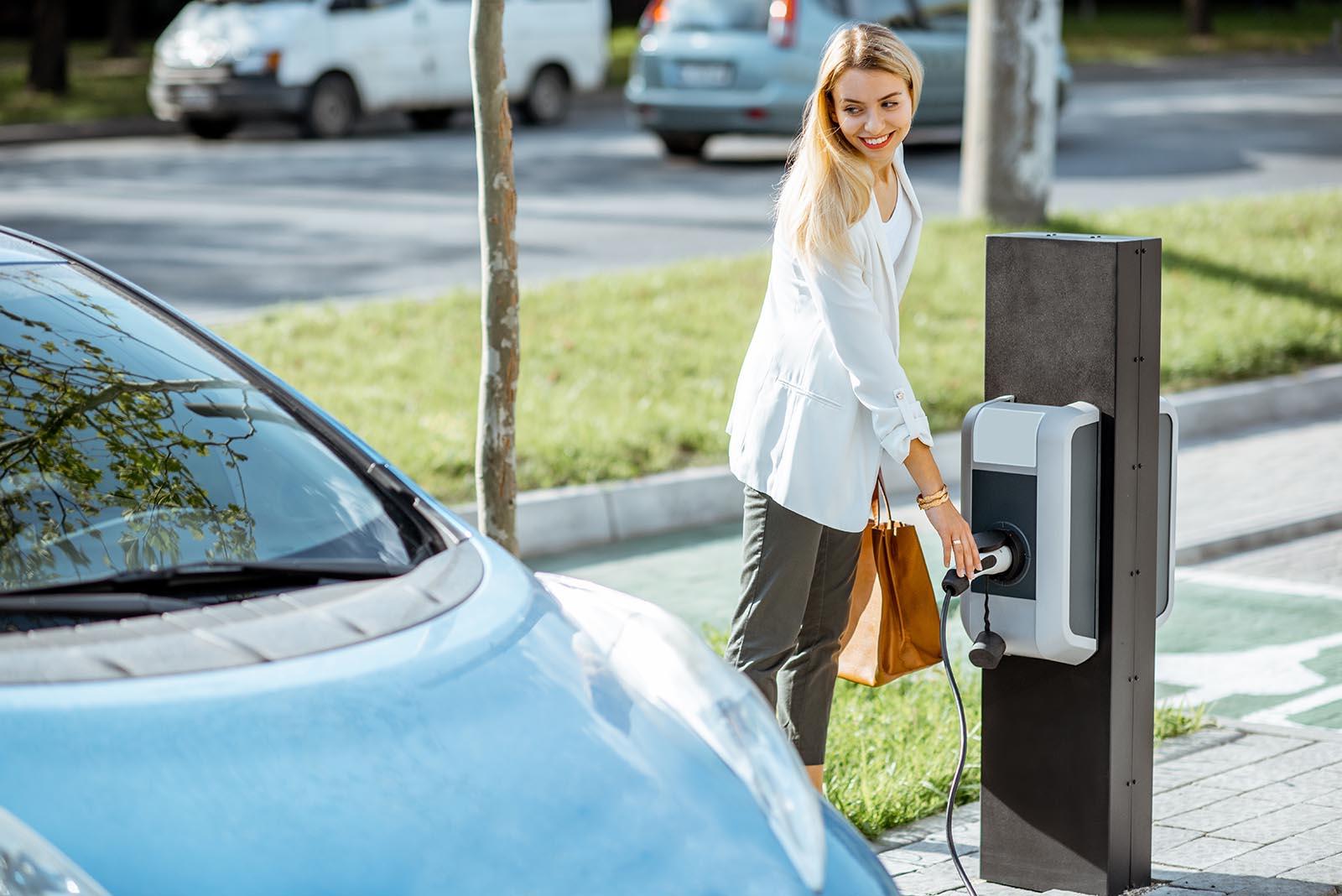 En kvinna sätter i kontakten i en laddstolpe för att ladda sin bil.
