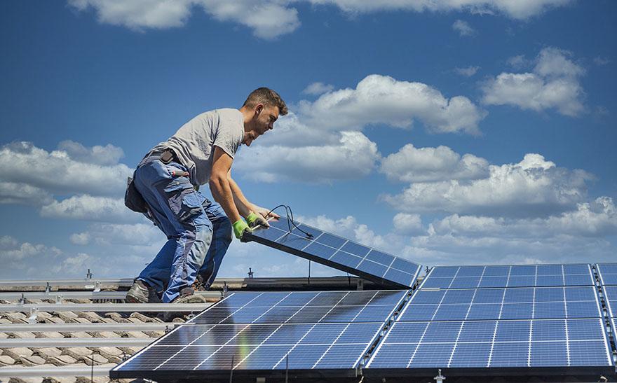 Två män installerar solceller på ett tak.