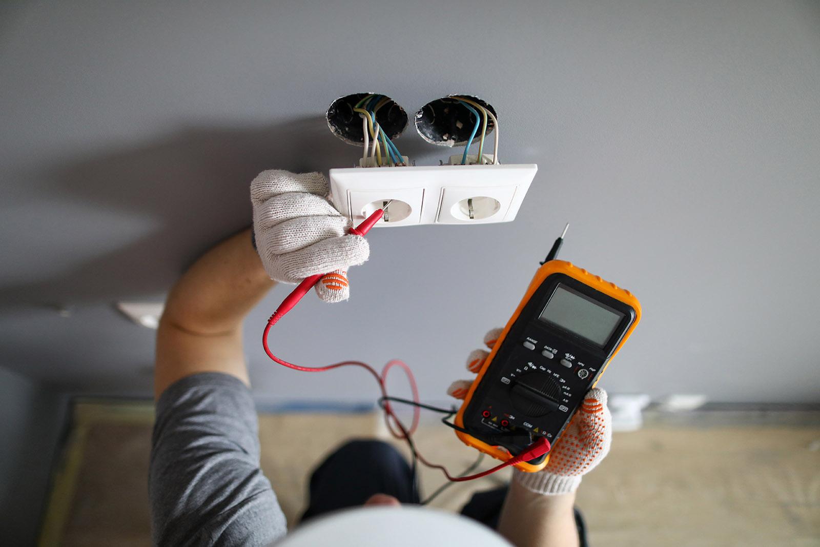 En elektriker som bär skyddshandskar kontroller ett vägguttag.